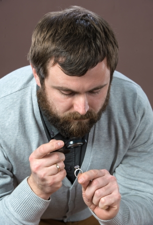 Man looking at jewelry through magnifying glass