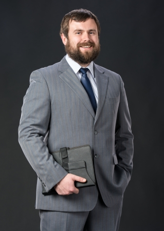 Businessman holding tablet pc on a gray background Stock Photo - 25025419