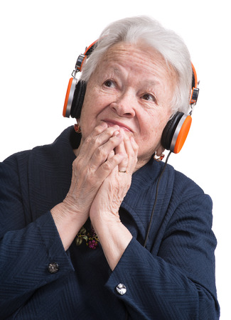 Old woman listening to music in headphones on a white