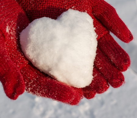 Hands in red gloves holding snow heart  写真素材