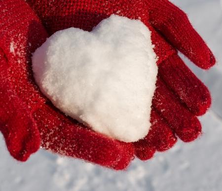 Handen in rode handschoenen bedrijf sneeuw hart