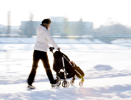 Mother walks with the child in the stroller  Intentional motion blur