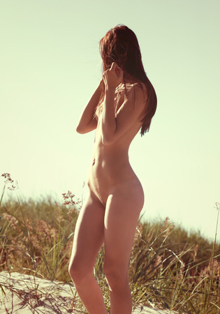 bare breast: Young naked woman on a sandy beach Intentional color shift