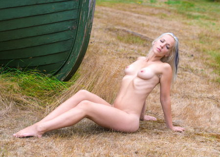 Young nude woman posing near  boat against the nature background photo