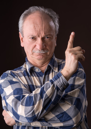 conform: Angry elderly man pointing up on dark background