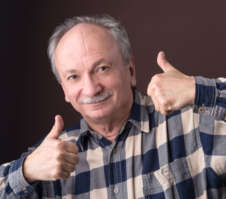 Happy elderly man showing ok sign on a brown background photo