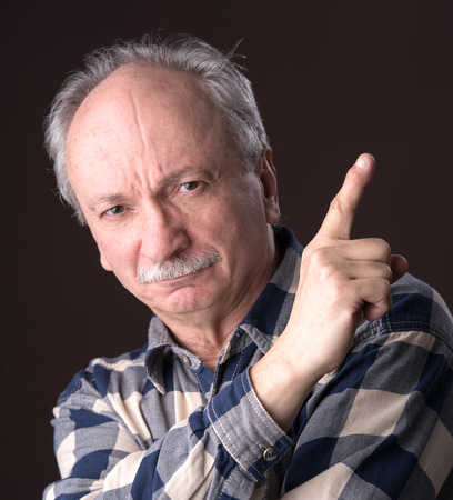 concur: Angry elderly man pointing up on dark background