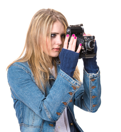 Girl in casual clothes taking picture with vintage film camera photo