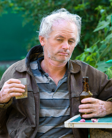 Drunk man drinking beer on natural background photo