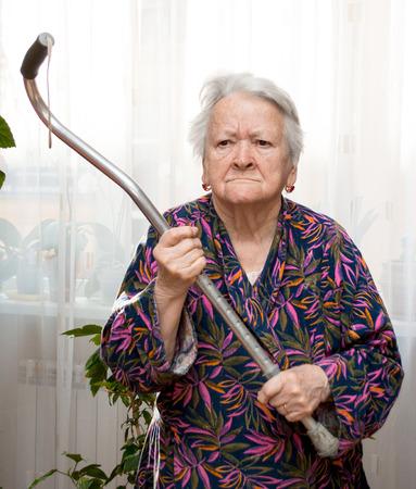 Oude boze vrouw bedreigt met een stok thuis Stockfoto