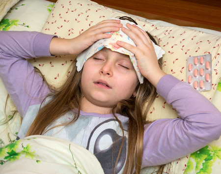 sick child: Sick girl lying in bed