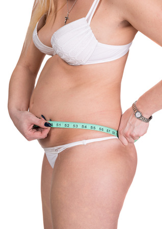 Overweight woman measuring waistline with centimeter on a white background  photo