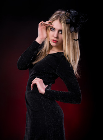 Young woman in black dress  on a dark red background photo
