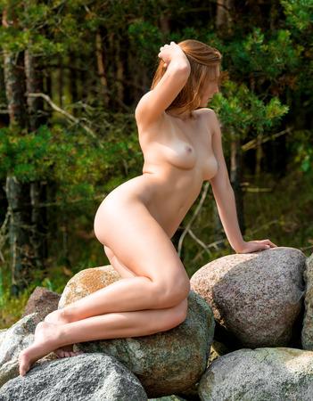 mujer desnuda sentada: Hermosa mujer desnuda sentada sobre las piedras contra el fondo la naturaleza