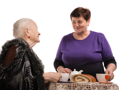 Mother having tea with her daughter on a white background photo