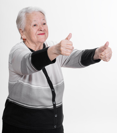 Old woman showing ok sign on a white  photo