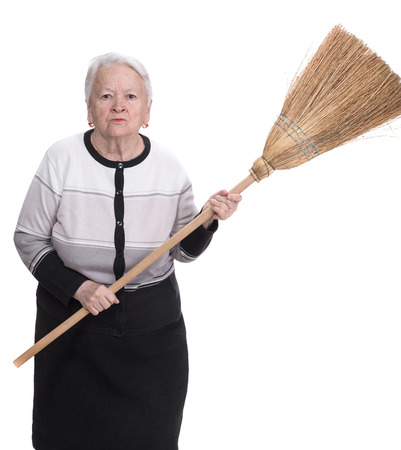 Old angry woman threatening with a broom on a white  photo
