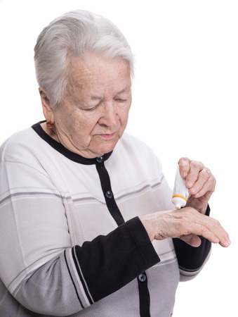 Old woman applying hand cream on a white background Stock Photo
