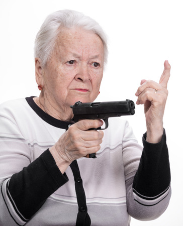 Old woman with pistol on a white  免版税图像