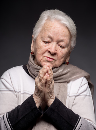 Old woman praying on a gray  photo
