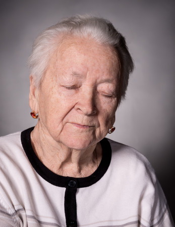 eye's closed: Portrait of old pensive woman with closed eyes  on a gray background