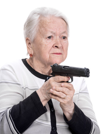 Old woman with pistol on a white background photo