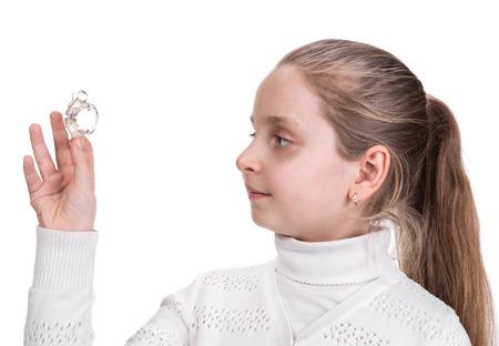 Girl holding dental braces over white