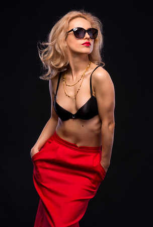 Beauty woman in red skirt and sunglasses on a dark background photo