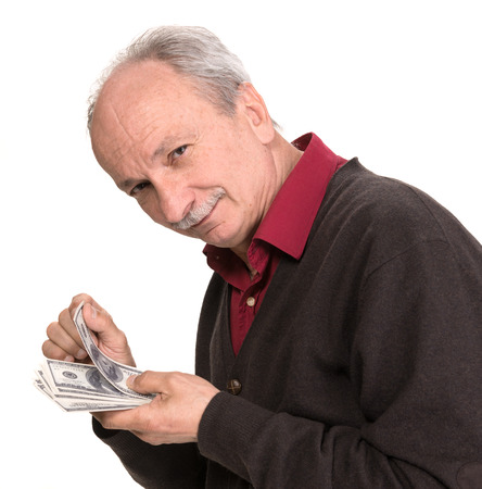 Senior man holding at dollar bills on a white background photo