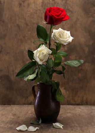 tallo: Rosas en un jarrón sobre un fondo de madera