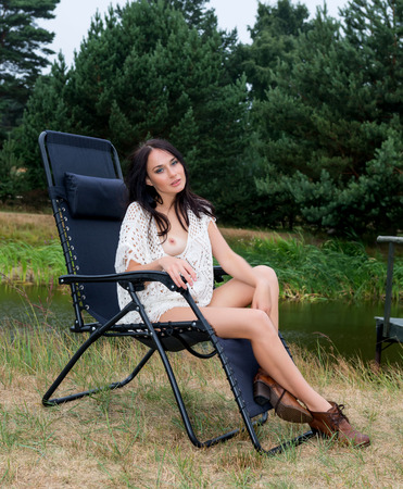 Young seminude woman sitting in the chair near a small pond photo