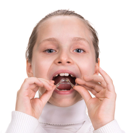 Girl putting on medical braces for orthodontic treatment over white Stock Photo - 27537618