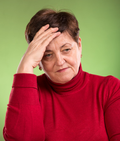 Mature woman suffering from headache on a green background Stock Photo