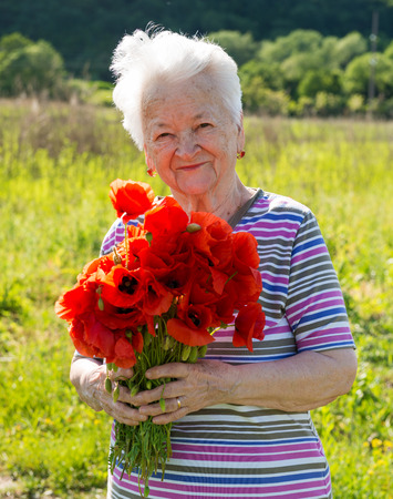 Old woman with bunch of poppies
