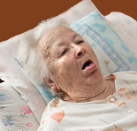 Sick senior woman coughing at bed