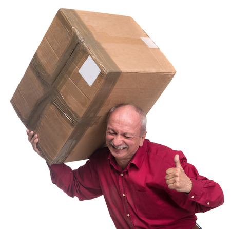 Senior man carries a heavy box on a white background photo