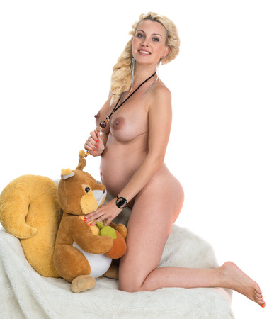 Naked pregnant woman with soft toy on a white  Stock Photo