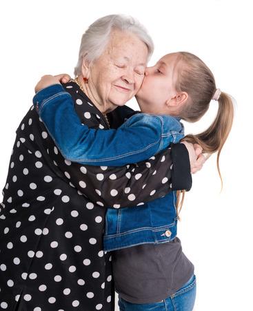 Granddaughter kissing her grandmother on white background