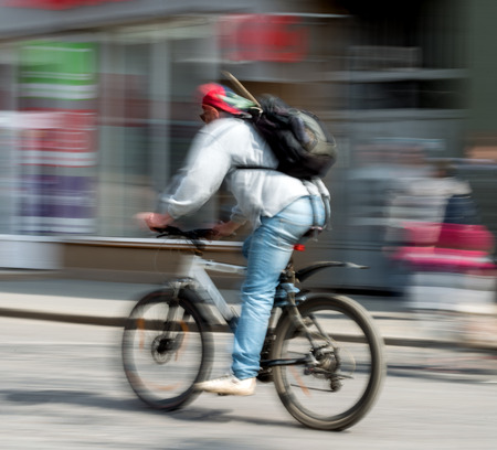 Cyclist in motion riding down the street   Intentional motion blur