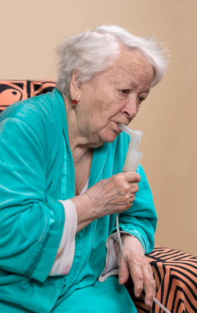 inhalation: Old woman making an inhalation at home