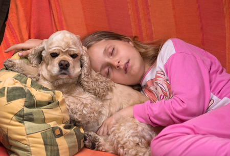 Girl and her dog sleeping together on a sofa photo