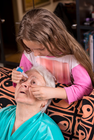 nosotrophy: Grandchild dripping eye drops to grandmother at home