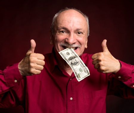 Happy elderly man holding dollar bill in the mouth Stock Photo