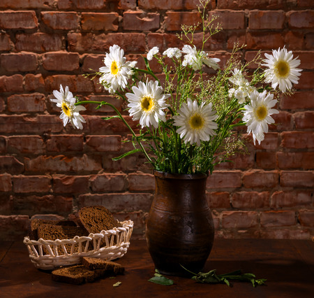 Bouquet of daisies in vase and bakery pieces of  bread photo