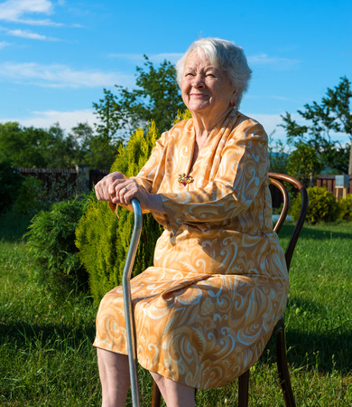 eighty: Old woman sitting on a chair with a cane in the garden