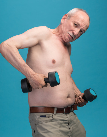 Senior man exercising with dumbbells on a blue background Stock Photo