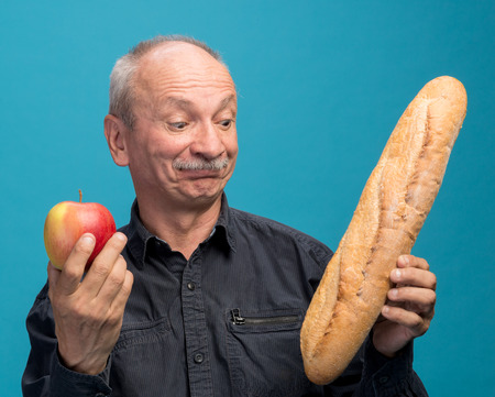 Doubting man with apple and baguette on a blue background photo