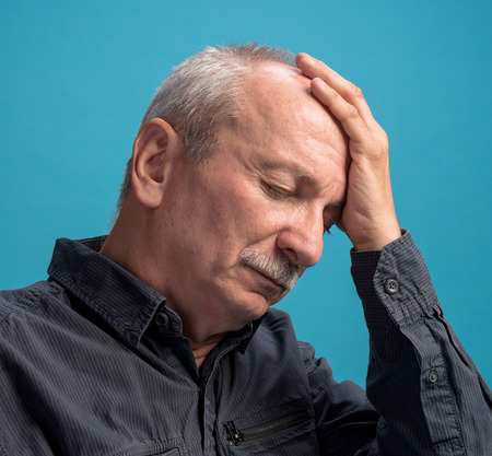 Headache  Portrait of senior man on a blue background Standard-Bild