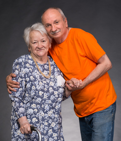 beloved: A grown son with his aging mom on a gray background