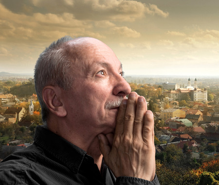 arrepentimiento: El hombre mayor orando contra el paisaje urbano